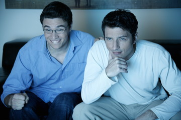Two men watching a game on television