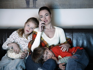 Mother and children watching television
