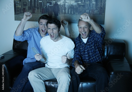 Three men watching a game on television