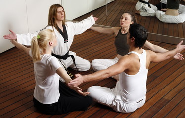 Participants in a fitness class practicing breathing exercises