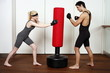 Young man and woman practicing with a punching bag