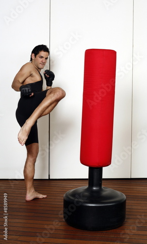 Young man kicking a punching bag