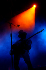 stage with light smoke and guitar player