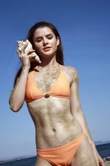 Female young adult in bikini listening to seashell