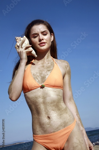 Female young adult in bikini listening to seashell