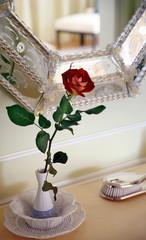 Dresser with rose in a vase