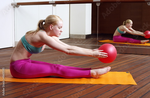 Young woman performing a pilates stretch with a ball