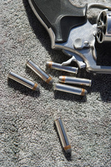 Hand gun and bullets on carpet, close-up