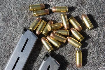 Gun magazine and bullets on carpet, close-up