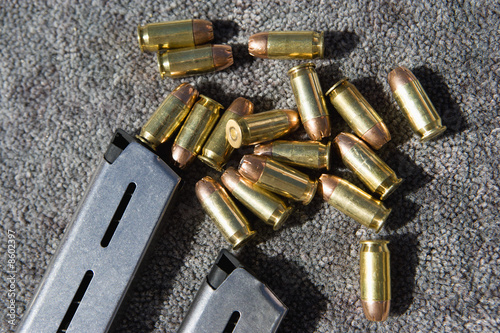Gun magazine and bullets on carpet, close-up