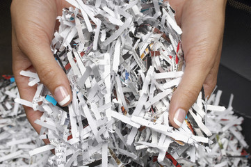 Woman holding heap of shredded paper, close-up of hands