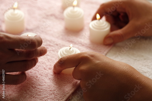 Hands with lit candles