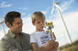 Boy 7-9 blowing toy windmill with father at wind farm