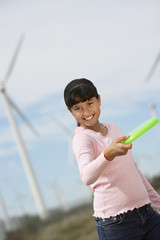Girl 7-9 throwing disc at wind farm, portrait