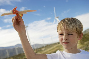 Boy 7-9 playing with toy glider at wind farm