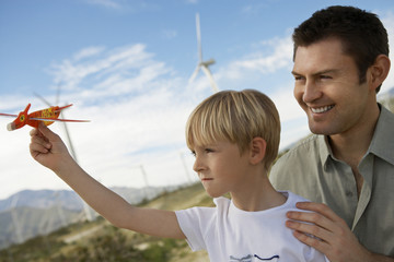 Boy 7-9 holding toy glider with father at wind farm