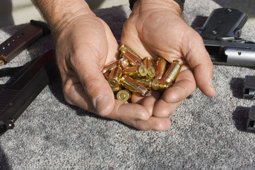 Mans hands holding bullets by guns, close-up