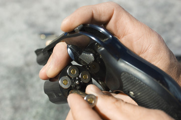 Man loading bullets into gun, close-up of hands