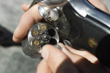Man loading bullets into gun, close-up of hands
