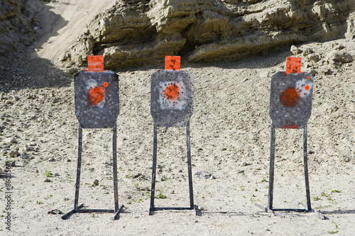 Three targets with bullet holes at firing range