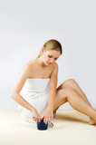 young woman with a towel is applying lotion poster