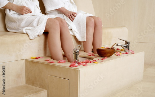Two young women enjoying a foot bath with rose petals