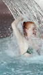 Young woman standing under water spray in spa pool