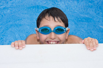 boy swimming in the pool with goggles and a big grin