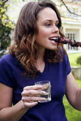 Woman eating souvlaki and drinking wine at a barbecue