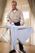 Mature man ironing shirt
