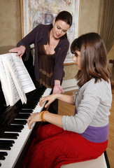 Woman teaching piano to girl