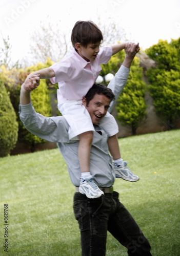 Man carrying a little boy on his shoulders