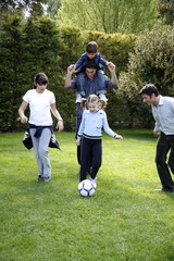 Man and children playing soccer