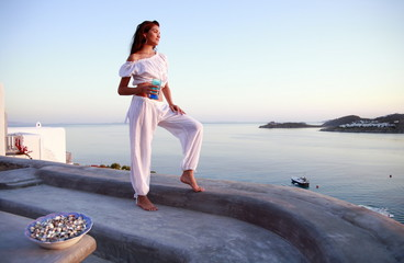 Woman in white outfit on terrace with a view