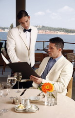 Man ordering from the menu to the waiter in restaurant