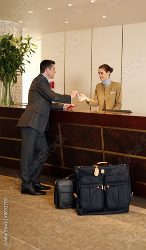 Man checking in  at the hotel reception desk