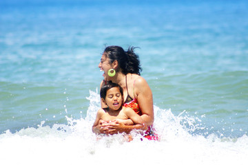 Mother Having Fun with Son in the Water at the Beach