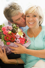 Husband giving wife flowers kissing and smiling