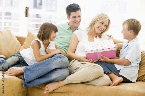 Family in living room with mother receiving gift and smiling