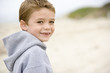 Young boy standing on beach smiling