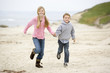 Two young children running on beach holding hands smiling