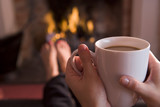 Fototapety Feet warming at a fireplace with hands holding coffee