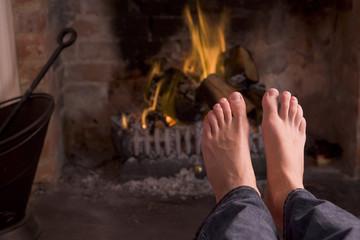 Feet warming at a fireplace