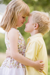 Two young children hugging outdoors