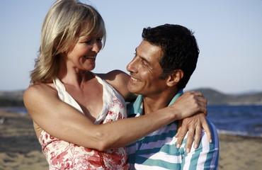 Mature adult couple hugging on beach