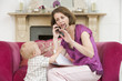 Mother using telephone in living room with baby frowning