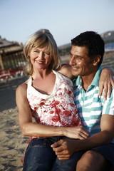 Mature adult couple sitting on beach