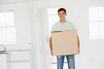 Man with box moving into new home smiling