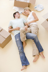 Couple lying on floor by open boxes in new home smiling