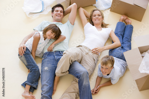 Family lying on floor by open boxes in new home smiling